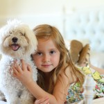 Maltese-and-girl on bed, gentle interaction between girl and dog