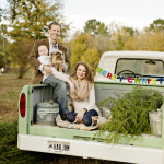 family Christmas photo with dog, old truck, Christmas tree