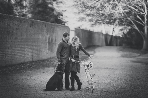 © Imagine It Photography | engaged couple with dog on gravel path, vintage bike, sunflowers, dog, engagement photos