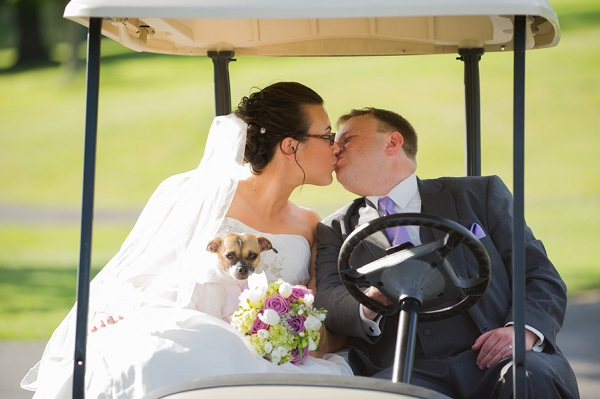 © Brittany Anderson Photography  | small brown white dog golf cart with bride-and-groom