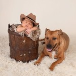 newborn photography session with dog, baby in cowboy hat and dog