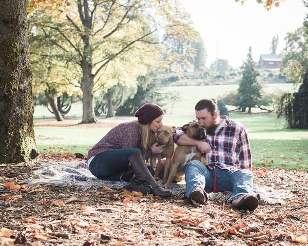 couple, pit bulls enjoying day at park