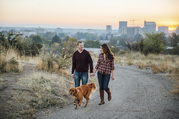 engagement photos with Golden Retriever, couple walking dog up hill away from city