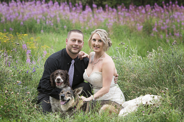 bride, groom, dogs sitting in meadow