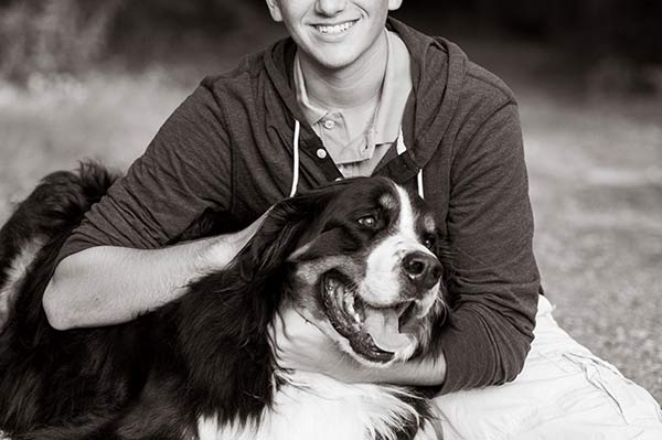 Bernese Mountain Dog smiling on teen's lap,