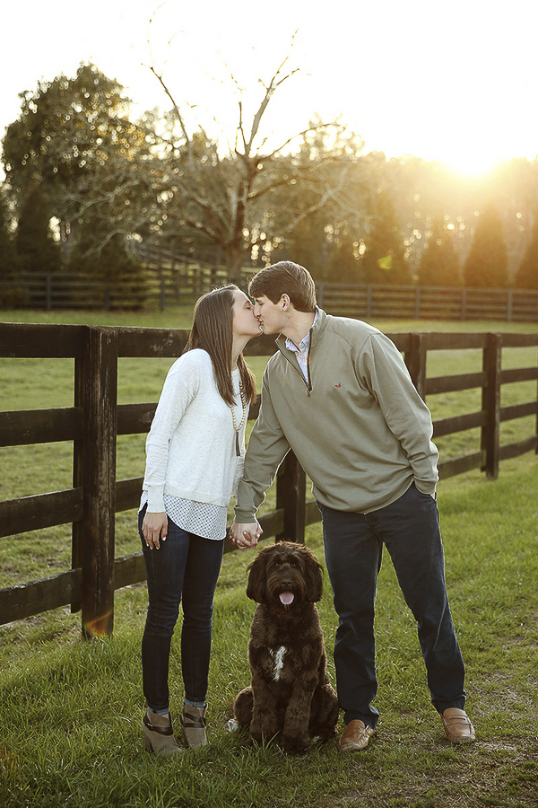 couple kissing with Labradoodle sitting between them