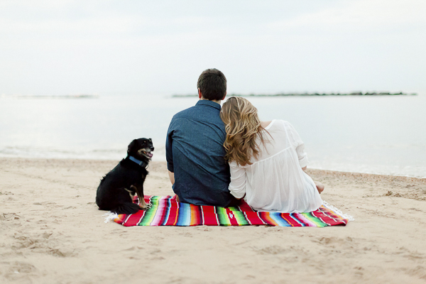 dog and couple sitting on colorful blanket at beach