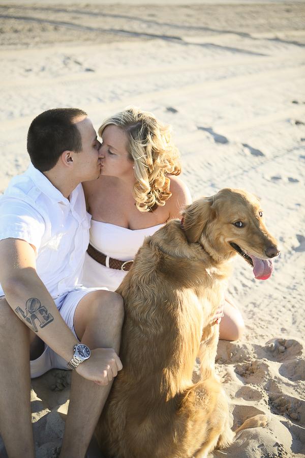 couple kissing, Golden Retriever sitting sandy beach