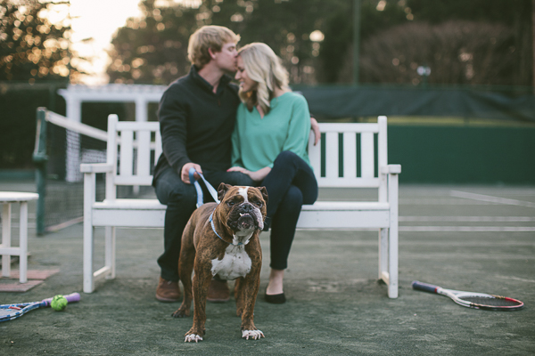 Snaggletooth English Bulldog tennis court engaged couple sitting on bench