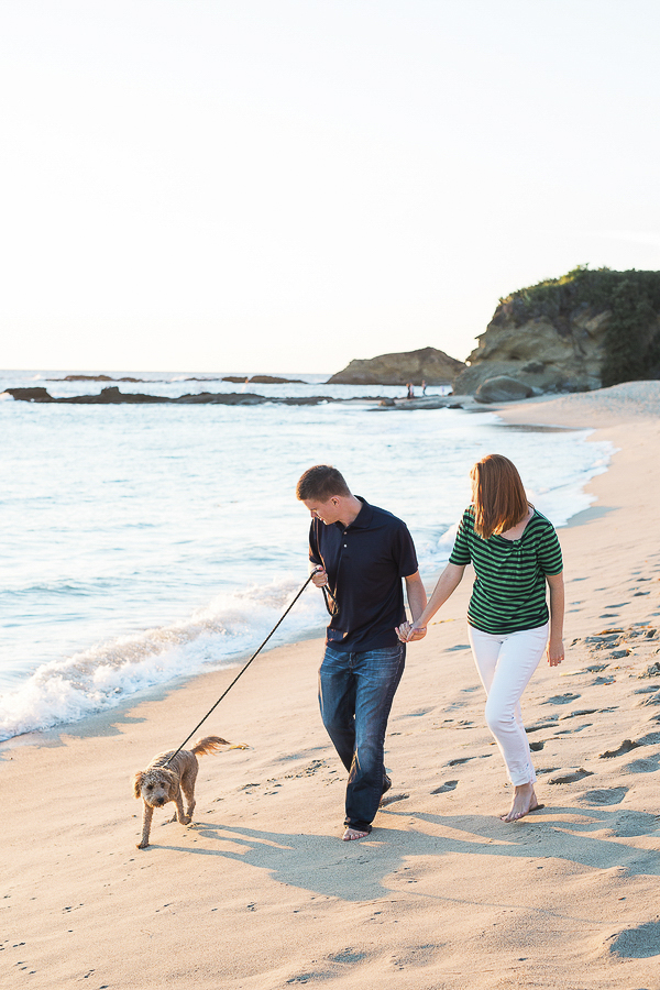 couple walking Golden Doodle puppy on beach
