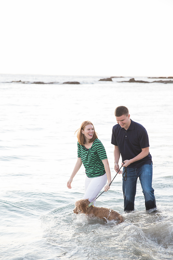 Happy couple and dog walking in shallow water, beach engagement photos