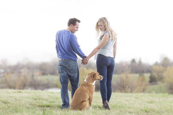 man, woman holding hands looking at dog