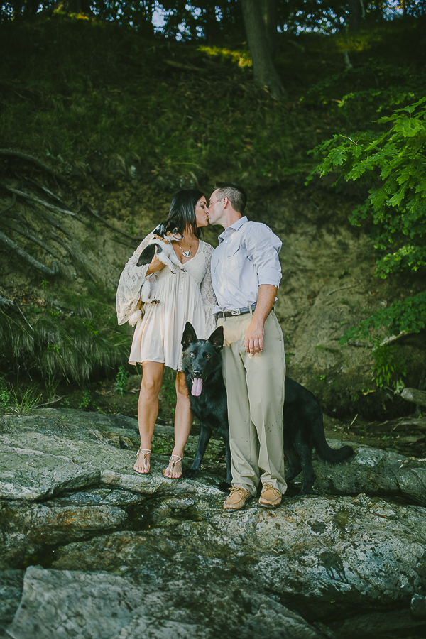 couple kissing on rock, including dogs in engagement photos