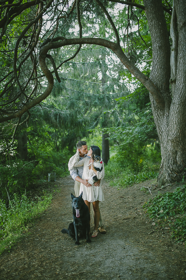 couple kissing in woods, black shepherd and Chi mix, ©Greta Tucker Photography