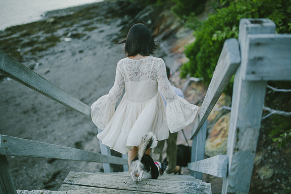 woman wearing white dress walking down steps to beach with dog