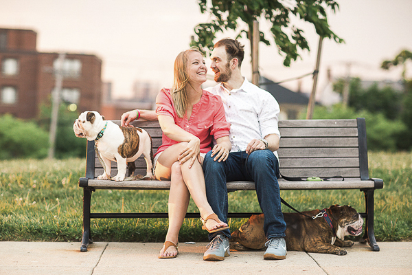 couple sitting with English Bulldogs on bench