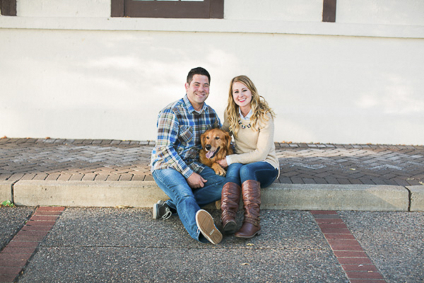 Golden Retriever sitting between people on curb, engagement photos with dogs