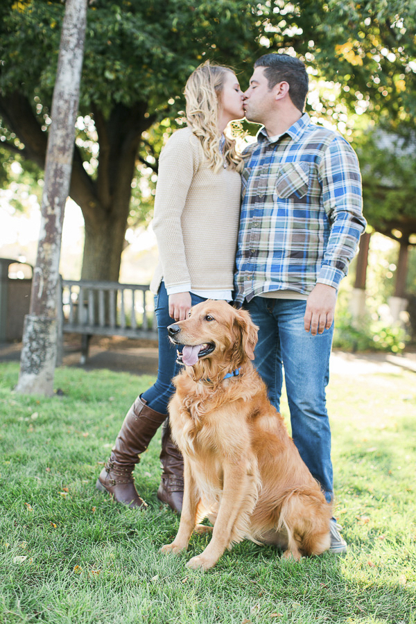 couple kissing at park, Golden Retriever sitting by their feet
