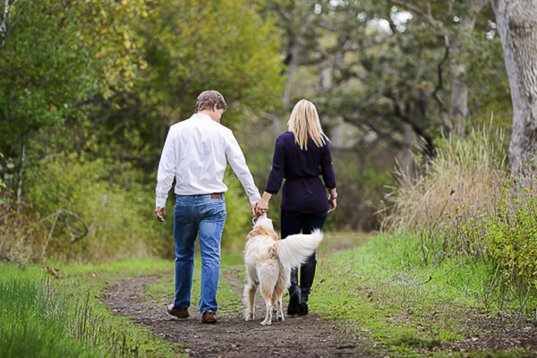couple holding hands walking with dog