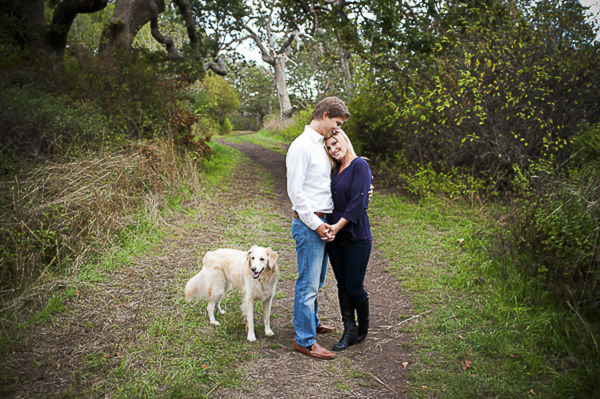couple standing on path with Retriever mix