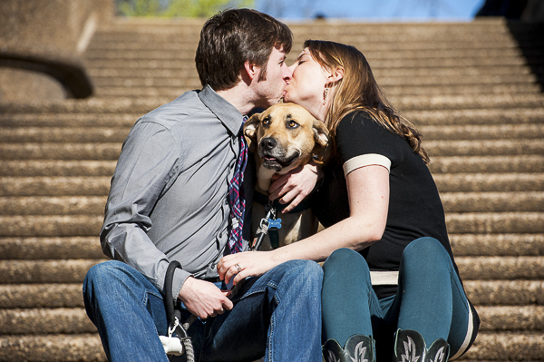 couple kissing on steps with hound between them,
