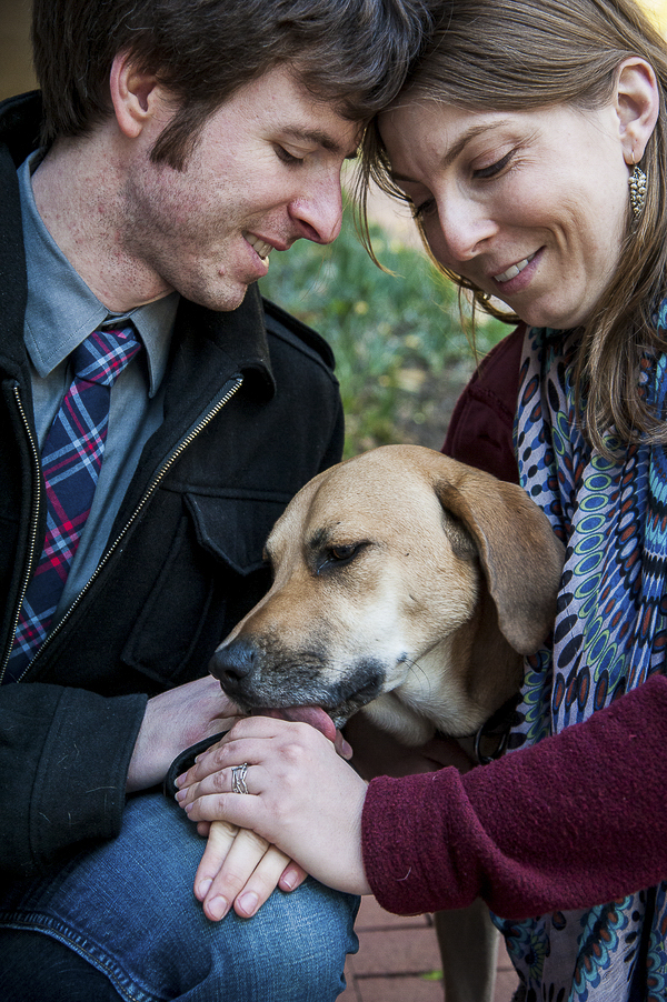 engaged couple smiling at dog, engagement pictures with dog