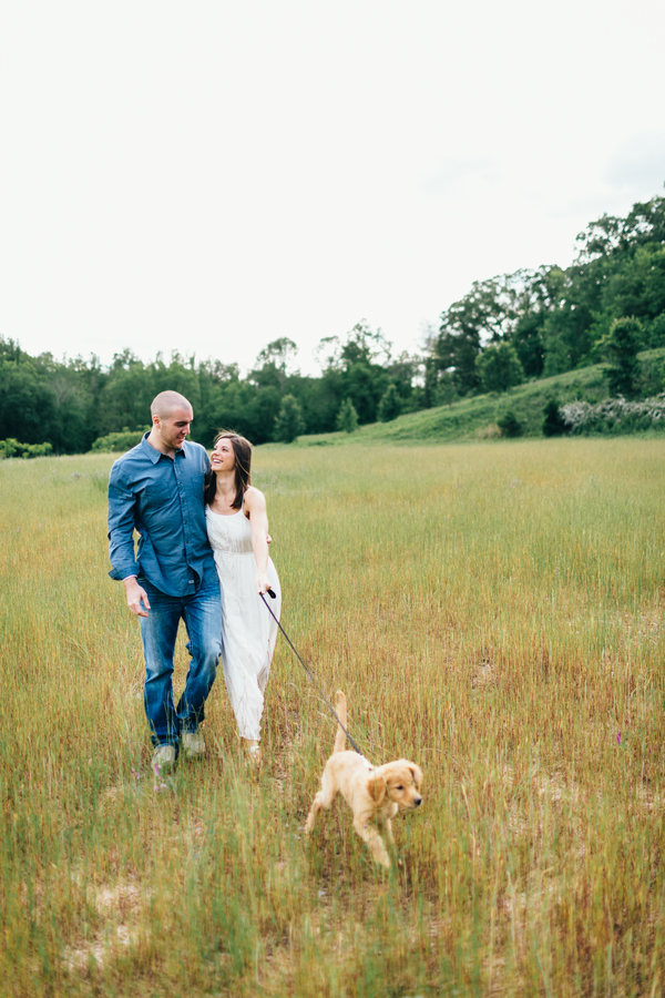 Erin Morrison Photography | couple walking retrieve puppy through a field