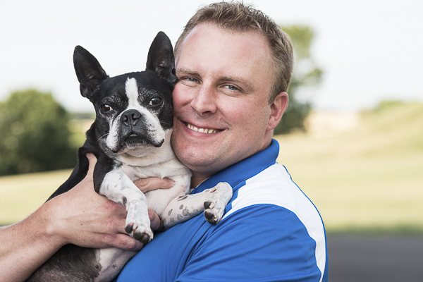 man holding Boston Terrier, man's best friend