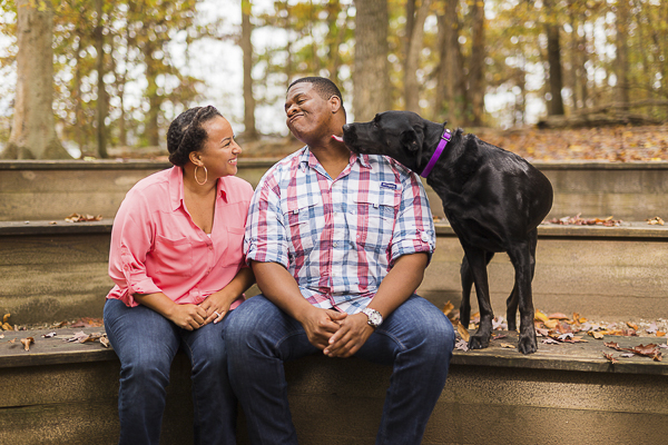 dog licking man's face, woman smiling, engagement-session-with-dog-