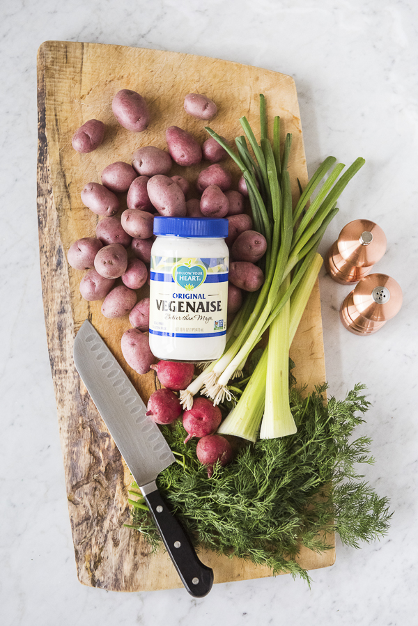 red potatoes, green onions, radishes, dill, knife on wood cutting board, copper salt shaker, copper pepper grinder, vegenaise