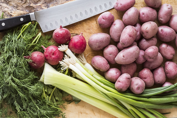 red potatoes, radishes, green onion, celery, dill on rustic wood cutting board