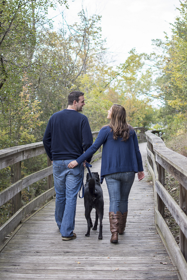 couple walking black dog on boardwalk