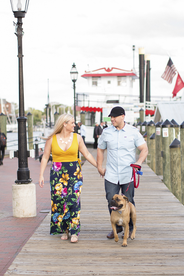 Boxer/Bulldog mix in bow tie, woman in floral dress, man in jeans, Annapolis waterfront engagement photos