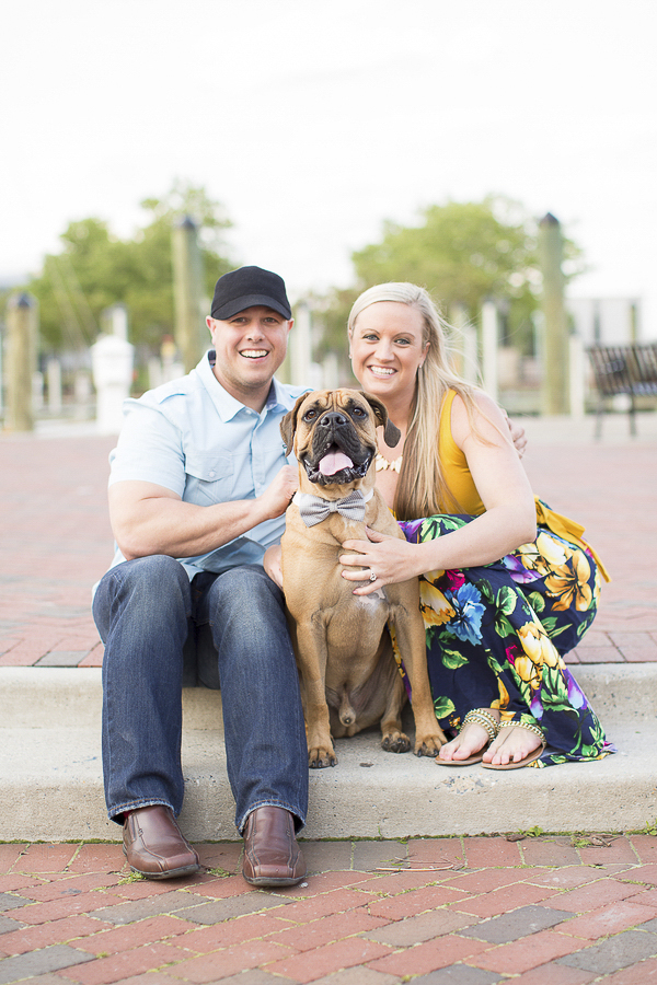 couple siting on curb with dog, Annapolis engagement photos