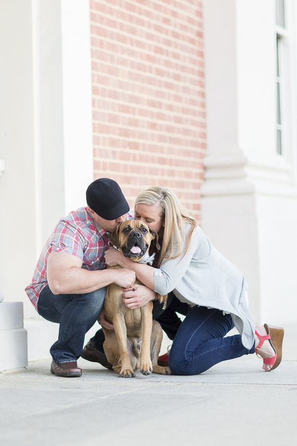 couple hugging Valley Bulldog (Boxer/English bulldog mix) in front of brick courthouse