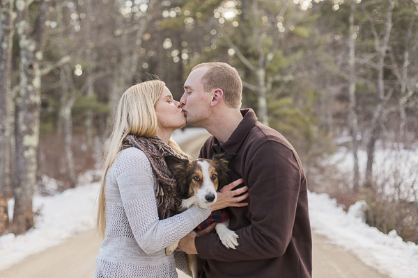 couple holding dog, winter engagement portraits with dog