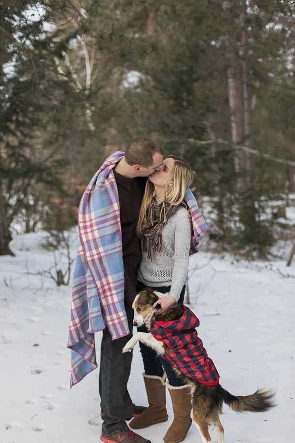 dog wearing plaid jacket with couple wrapped in blanket, winter engagement photos with dog