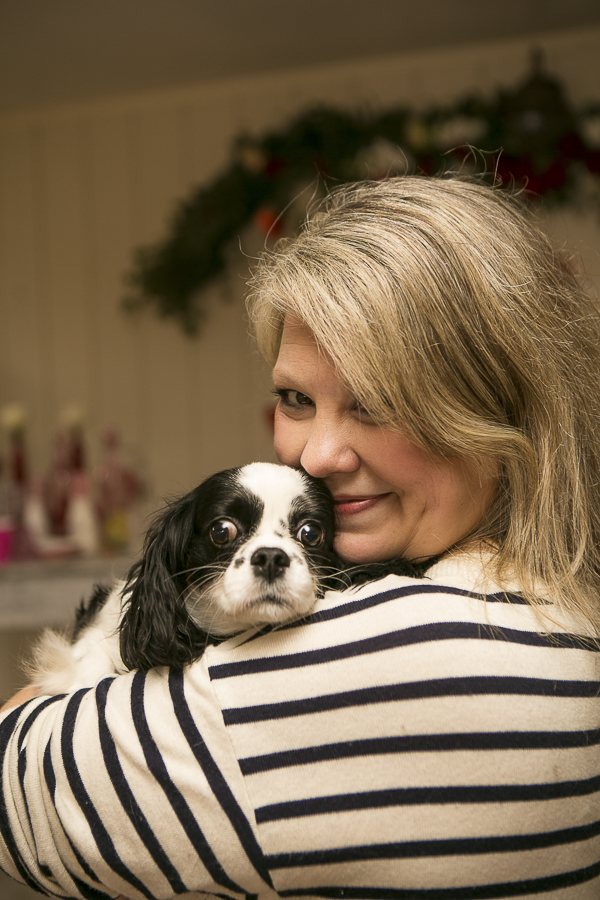 Cavalier King Charles spaniel snuggling on woman's shoulder