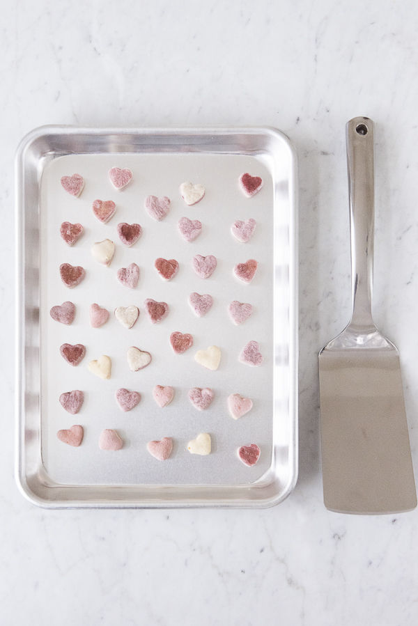 baking sheet filled with heart shaped dog treats, metal spatula
