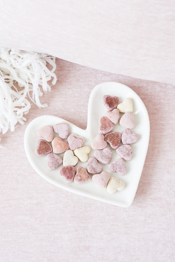 white ceramic heart plate with small pink and white heart shaped dog cookies, banana, beet dog treats