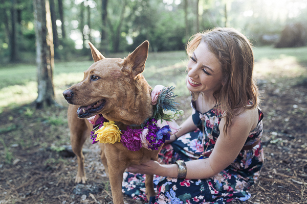 smiling dog in floral wreath, woman in sleeveless floral dress, celebrating human-dog bond