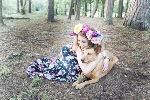 woman with floral crown hugging dog outside, lifestyle dog-human photos
