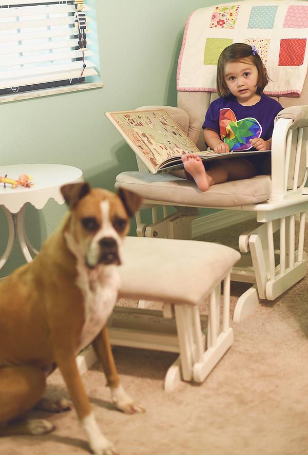 little girl reading story to dog, human-dog bond,