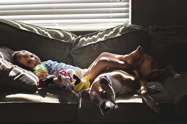 girl resting on sofa with dog and Mickey Mouse toy