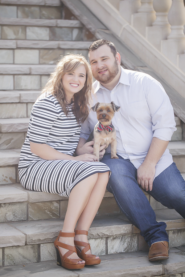 happy couple sitting on steps with Yorkie in laps