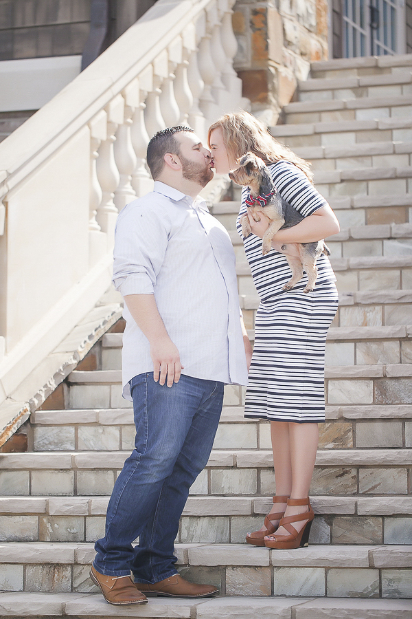 woman holding Yorkie kissing fiance on stone staircase