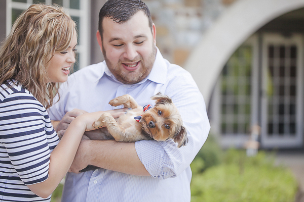 man holding Yorkie, woman looking at dog, engagement photos with dog