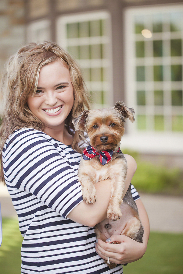 smiling blond in striped dress holding cute Yorkie wearing bow tie
