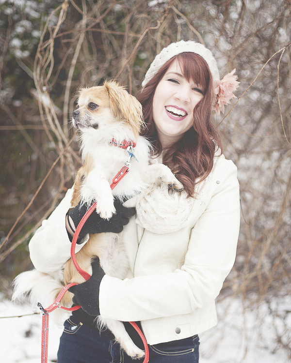 smiling woman holding small dog, snowy lifestyle dog photos
