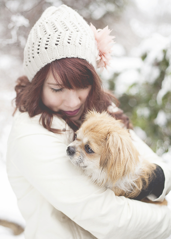 woman snuggling small dog outside, winter dog portraits
